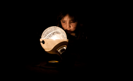 A girl gazes into a lighted globe, showing the solar system.