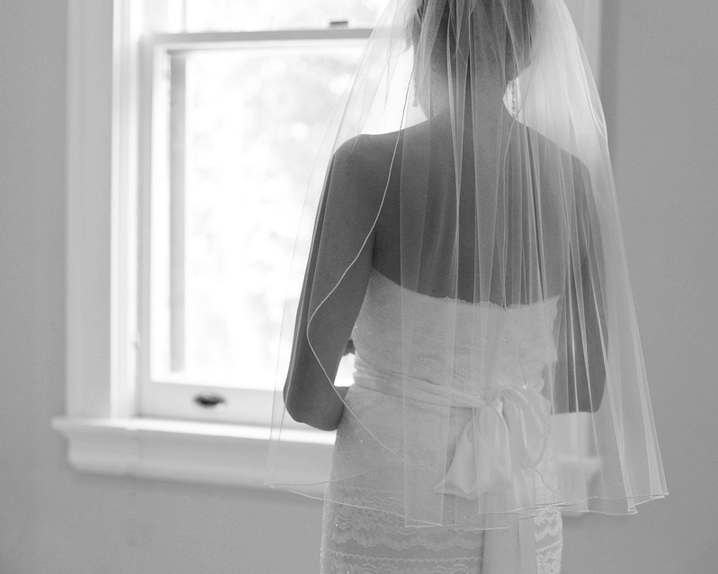 A bride, dressed for her wedding, looks out a window.