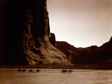 Seven riders on horseback and dog trek against background of canyon cliffs, by Edward Curtis