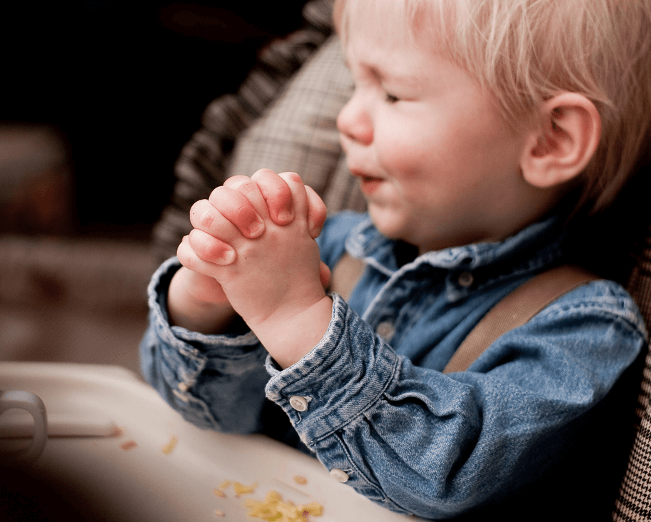 A little boy, hands clasped tightly and eye squinched shut, says his prayers.
