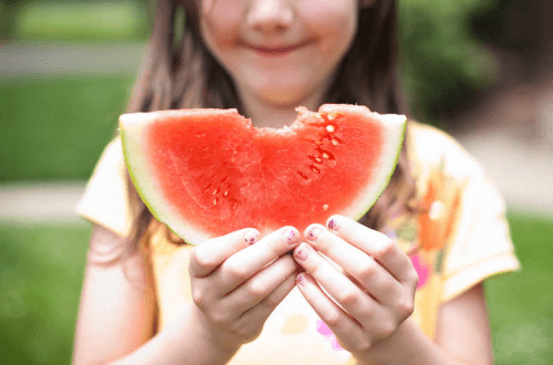 A girl holds a piece of watermelon with a nice bite take out of the edge of it.